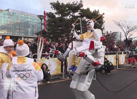 聖火リレー 搭乗型ロボットがランナーに