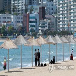 Жители Пусана спасаются от жары у моря