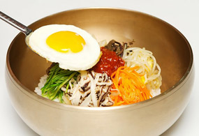 Put cooked rice in a large bowl and top it neatly with the stir-fried vegetables in order. Add a spoonful of seasoned red pepper paste in the center and finally top it with the fried egg.