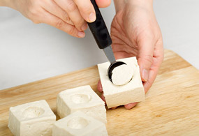 Quarter one block of tofu to the size of 5x5x3. Use a small spoon to scoop out a hole in each tofu piece and sprinkle the inside of the holes with corn starch.