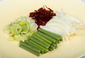 Cut dried chili peppers into 0.5-centimeter pieces, onions into 1-centimeter-thick slices, garlic sprouts into 5-centimeter pieces, and diagonally slice green onion into 0.5-centimeter pieces.