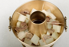 First fill the sinseollo vessel with white radish and extra beef slices, and smooth out the top.